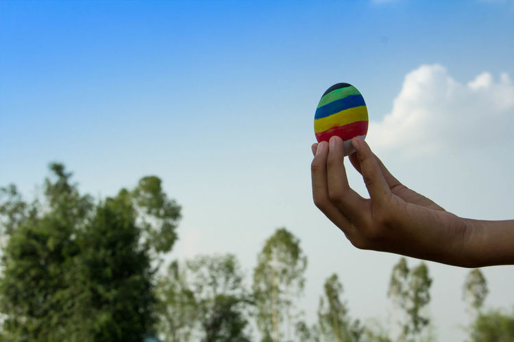 Low angle view of person hand holding multi colored egg against sky