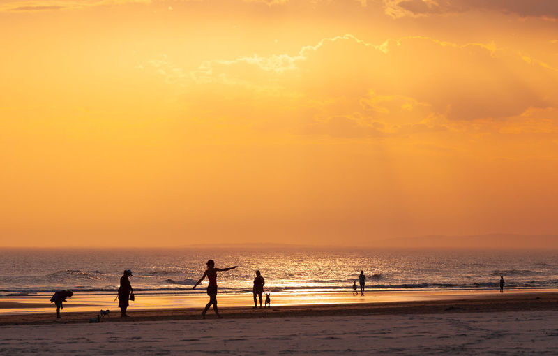 Silhouette people at beach against sky during sunrise
