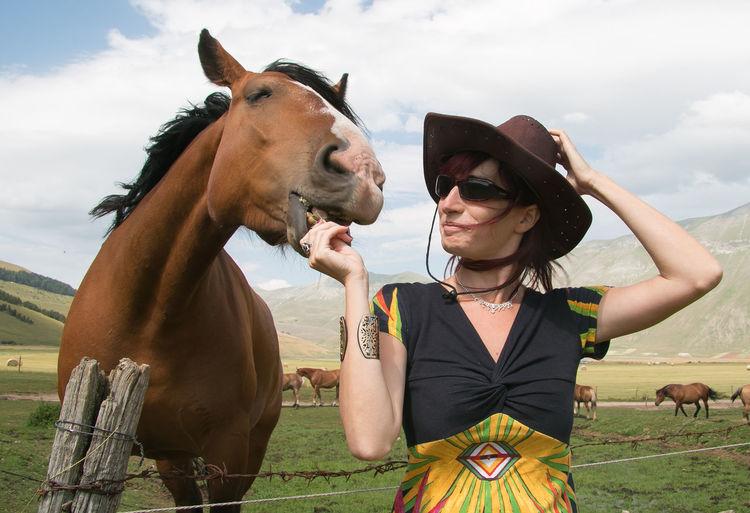 Woman feeding horse at ranch