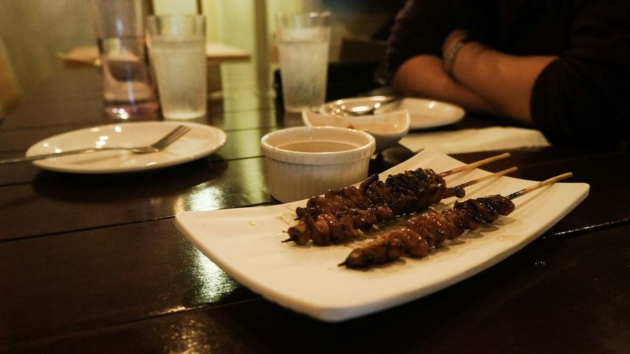 Close-Up Of Chicken Meat In Skewers Served On Table
