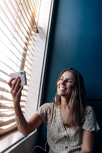 Portrait of smiling woman using mobile phone