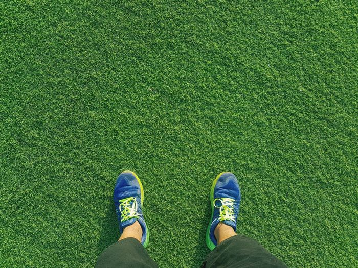 Low Section Of Person Wearing Sports Shoes Standing On Grassy Field