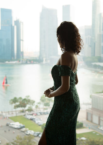 Side View Of Female Model Standing In Evening Gown By Window At Home