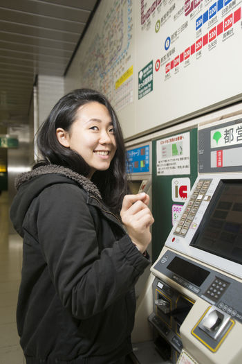 A young Japanese lady in the Tokyo subway. Cheerful Japan Japanese  Smiling Subway Station Technology Ticket Machines Tokyo Touch Screen Waist Up Woman