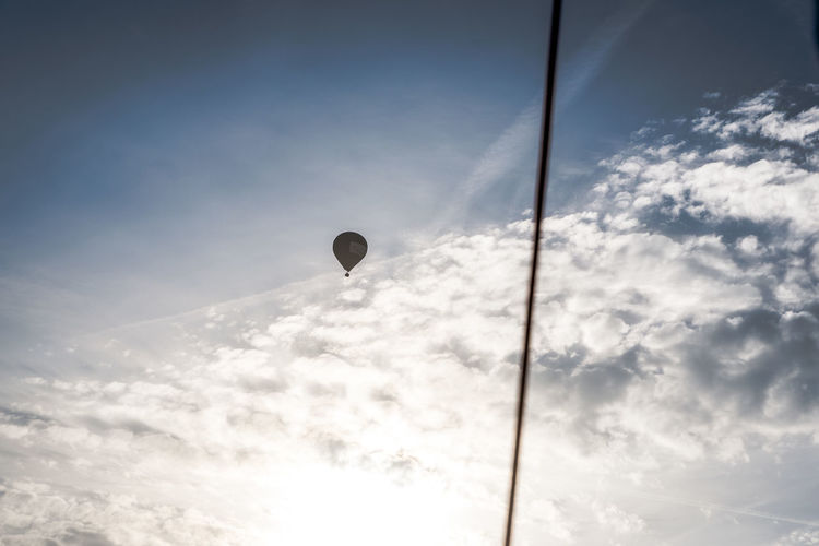 Air Vehicle Balloon Beauty In Nature Cloud - Sky Day Flying Hot Air Balloon Lighting Equipment Low Angle View Mid-air Nature No People Outdoors Scenics - Nature Silhouette Sky Sport Street Light Sunlight Transportation