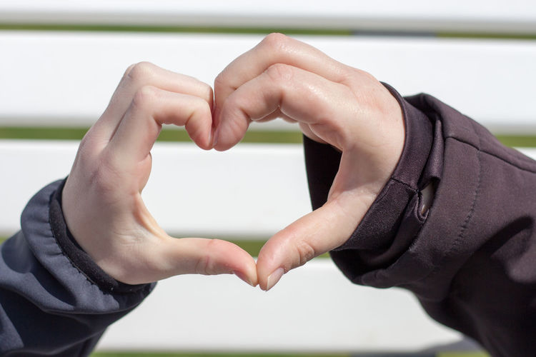 Cropped image of couple forming heart shape against wall