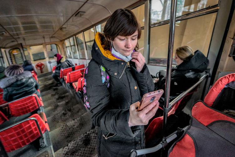 Full length of man using mobile phone at train