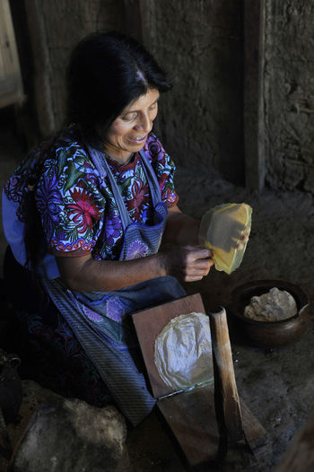 Cooking Front View Full Length Girls Holding Huipil Indoors  Leisure Activity Lifestyles Mexico Person San Juan Chamula Sitting Standing Three Quarter Length Traditional Cooking Traditional Culture Tzotzil Woman