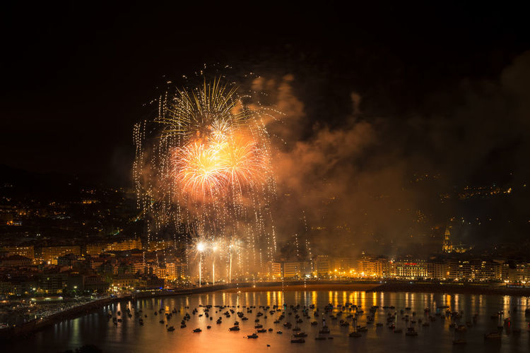 Firework display over river at night