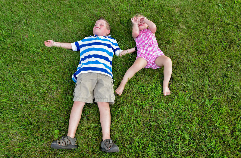 High angle view of children lying on grass