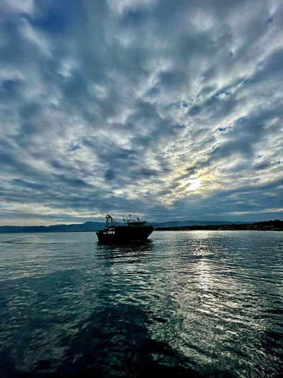 Boat sailing on sea against sky