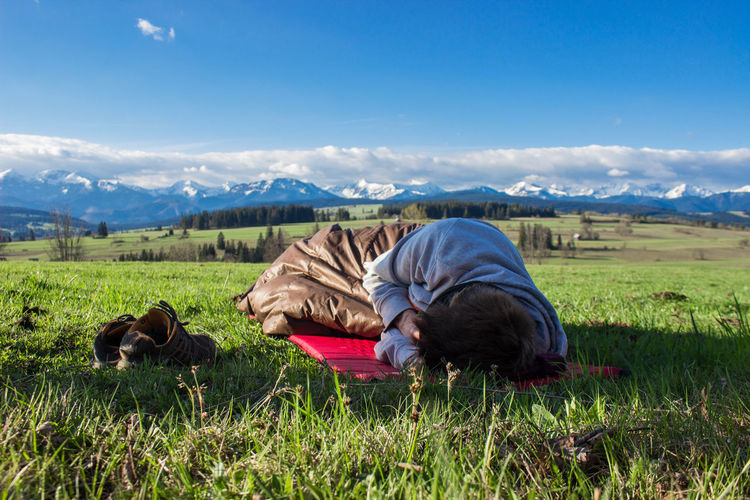 Young Man Sleeping On Green Sunny Field
