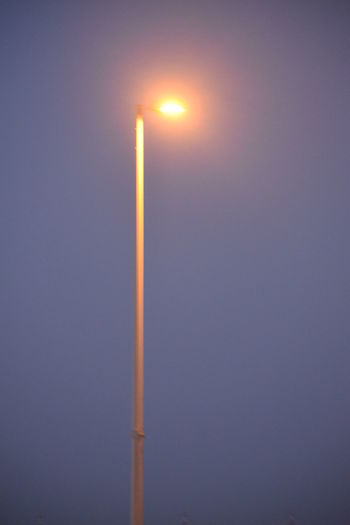Low angle view of illuminated street light against clear sky during sunset
