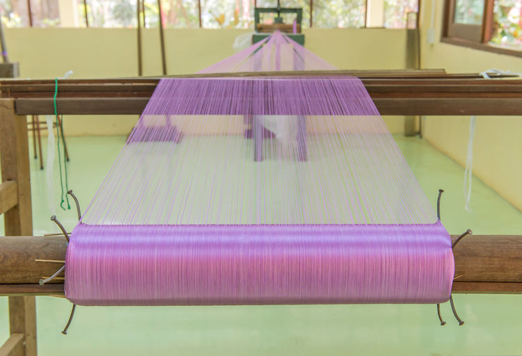Indoors  No People Thread Focus On Foreground Textile Close-up Art And Craft Loom Still Life Pink Color Spool Purple Wood - Material Table Equipment Textile Industry Day Industry Creativity Seat
