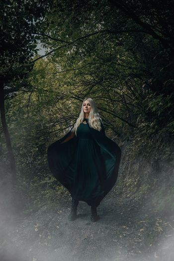 Woman dressed as a witch in a forest