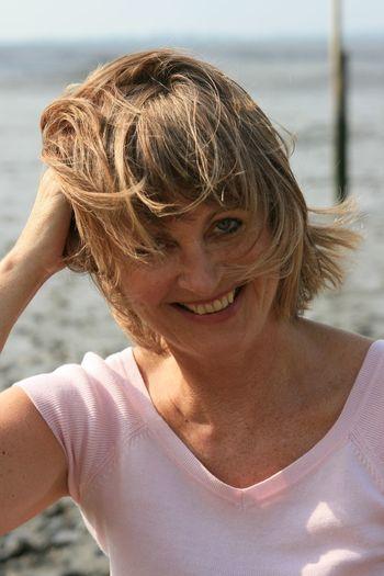 Portrait Of Smiling Senior Woman At Beach