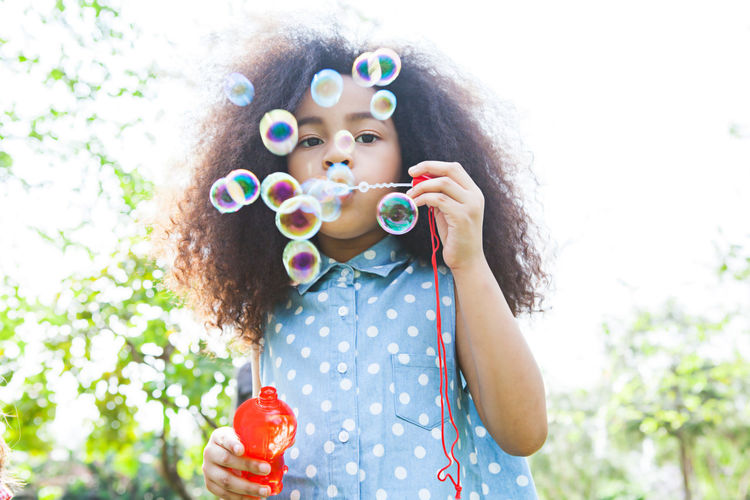 Portrait of girl blowing bubbles against sky