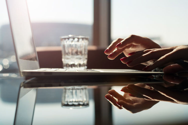Business woman using laptop at sunny day Human Hand Human Body Part Hand Using Laptop Technology Using Keyboard Focus On Foreground Lifestyles Real People Golden Hour Reflection Business Finance And Industry Leisure Activity Wireless Technology Communication Body Part Finger Close-up Table One Person Copy Space Laptop Using Computer