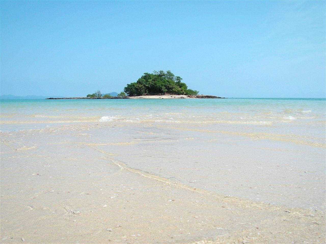 Surface level of calm beach against clear blue sky