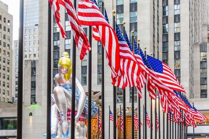 Jeff Koons New York Rockfeller Center USA Architecture Building Exterior Built Structure City Day Flag Low Angle View Modern Art Outdoors Patriotism Seated Ballerina Skyscraper Stars And Stripes