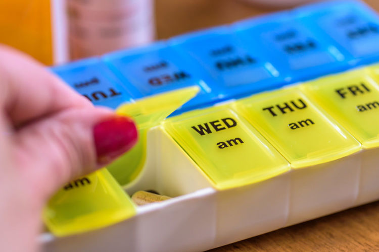 Cropped hand of woman taking pills in container with text on table