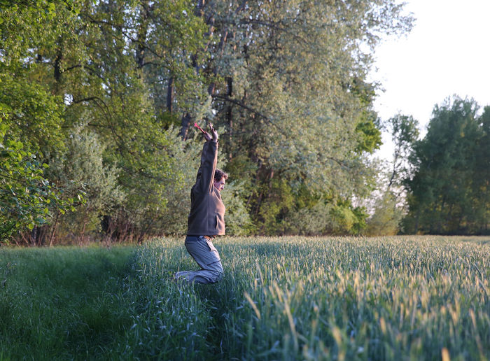 Side view of man jumping on grassy field