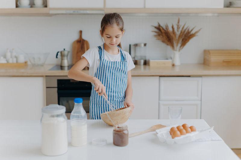 Girl preparing food on kitchen island at home