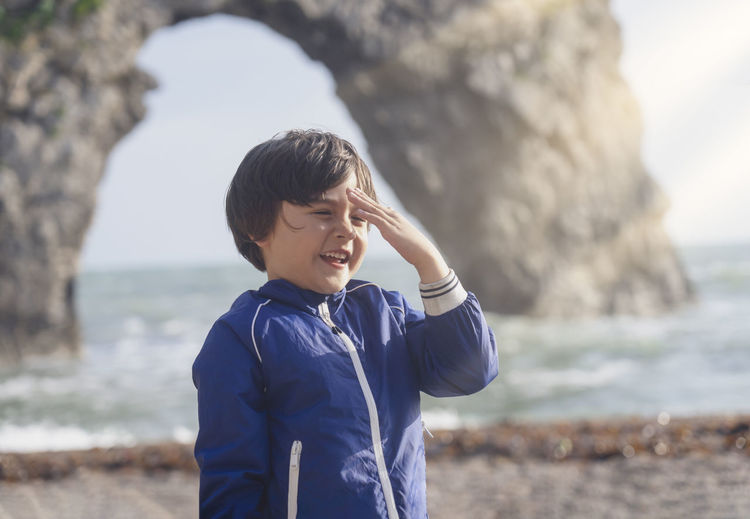 Cute smiling boy standing on beach