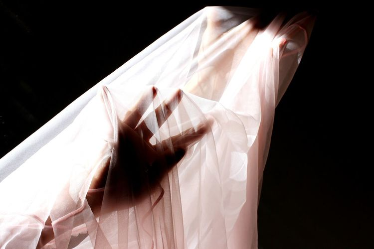 Cropped hand hand of woman with textile against black background