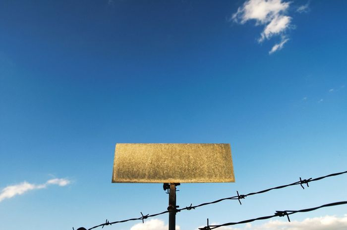Thorn Wire Fencing Fence Fences & Beyond Day Outdoors Road Sign Clear Sky Blue No People Low Angle View Rusty Sky