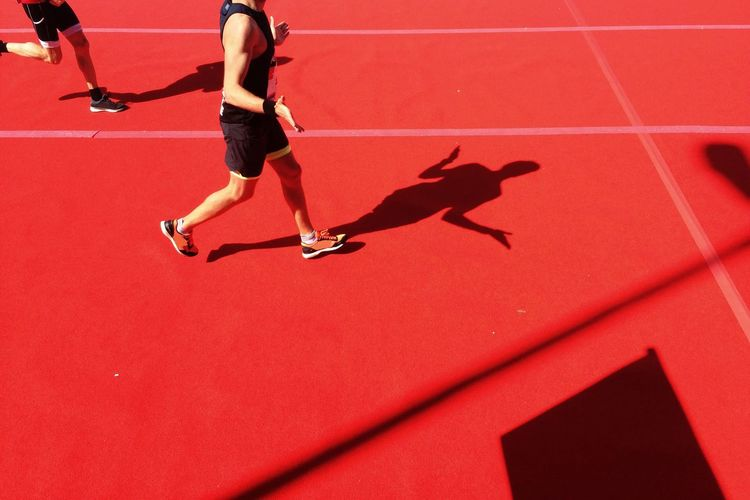 Low section of runner gesturing on running track