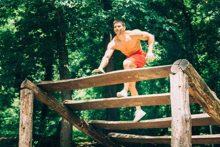 Full Length Of Shirtless Man Exercising On Wooden Platform