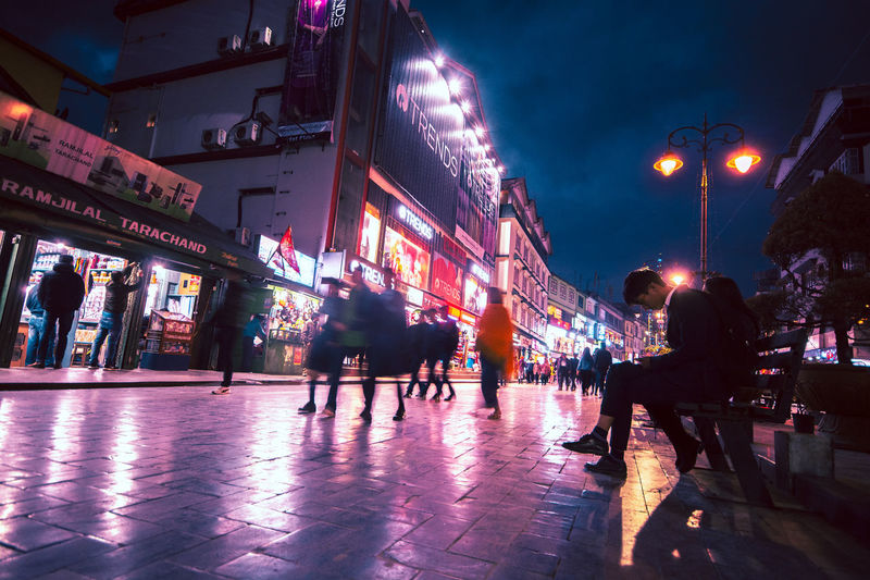 Illuminated City Street Night Building Exterior Group Of People Architecture Real People Built Structure City Life Women Walking Lifestyles Men Adult Large Group Of People Transportation Crowd Leisure Activity City Street Outdoors