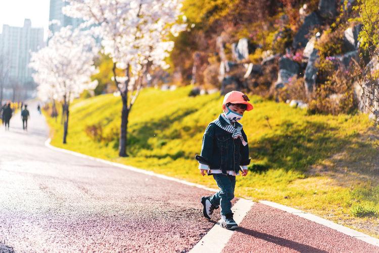 Rear view of boy walking on road in city