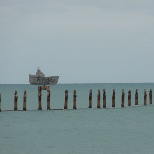 Wooden Posts Amidst Sea Against Sky