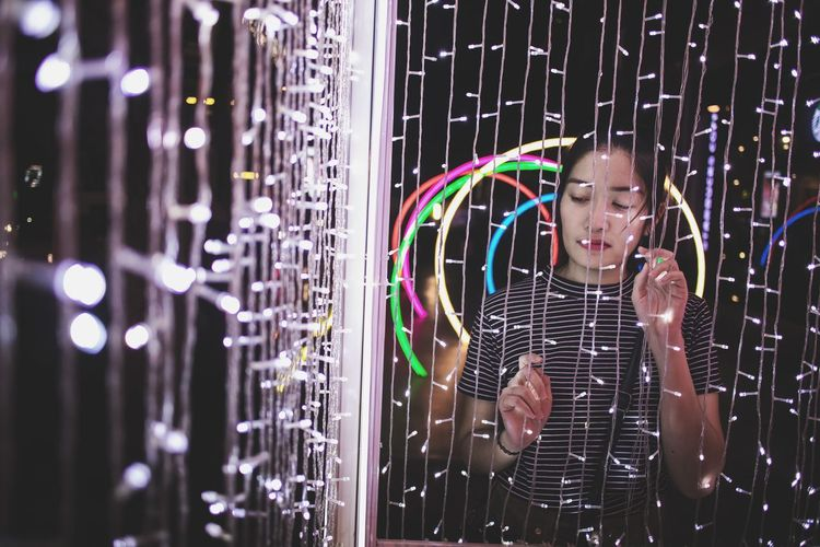 Young Woman Standing By Illuminated String Lights In Room