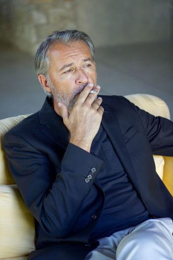 Man smoking cigarette looking away while sitting on sofa