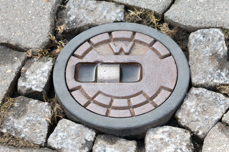 Round street cap for gate valve of a water pipe Close-up Day Lid Manhole  Nature No People Outdoors Pebble Rock - Object Sewage Stone - Object Street Cap