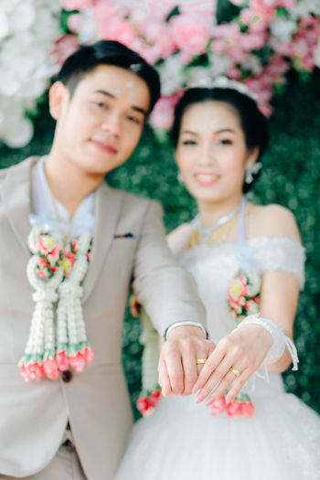 Portrait Of Smiling Bride And Groom Showing Rings During Wedding