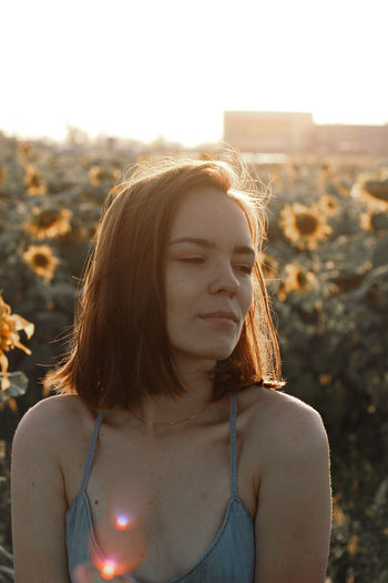 Beautiful woman looking away against sunflower plants at farm