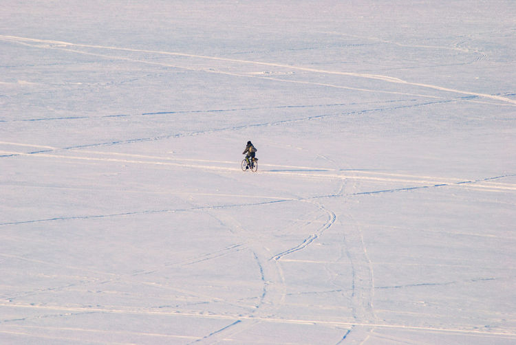 High Angle View Of Person Riding Bicycle On Snowy Field