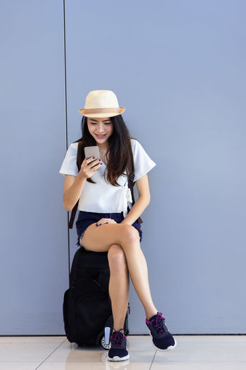 Young woman using phone while sitting on luggage against wall