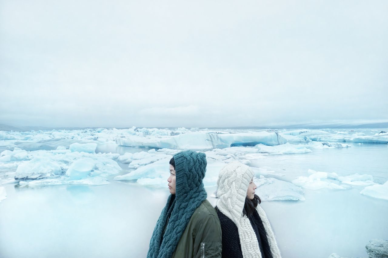 Women in warm clothing standing over frozen landscape against clear sky