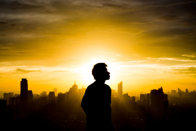 Silhouette man against cityscape during sunset