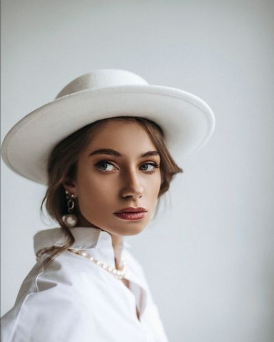 Portrait of young woman wearing hat against white background