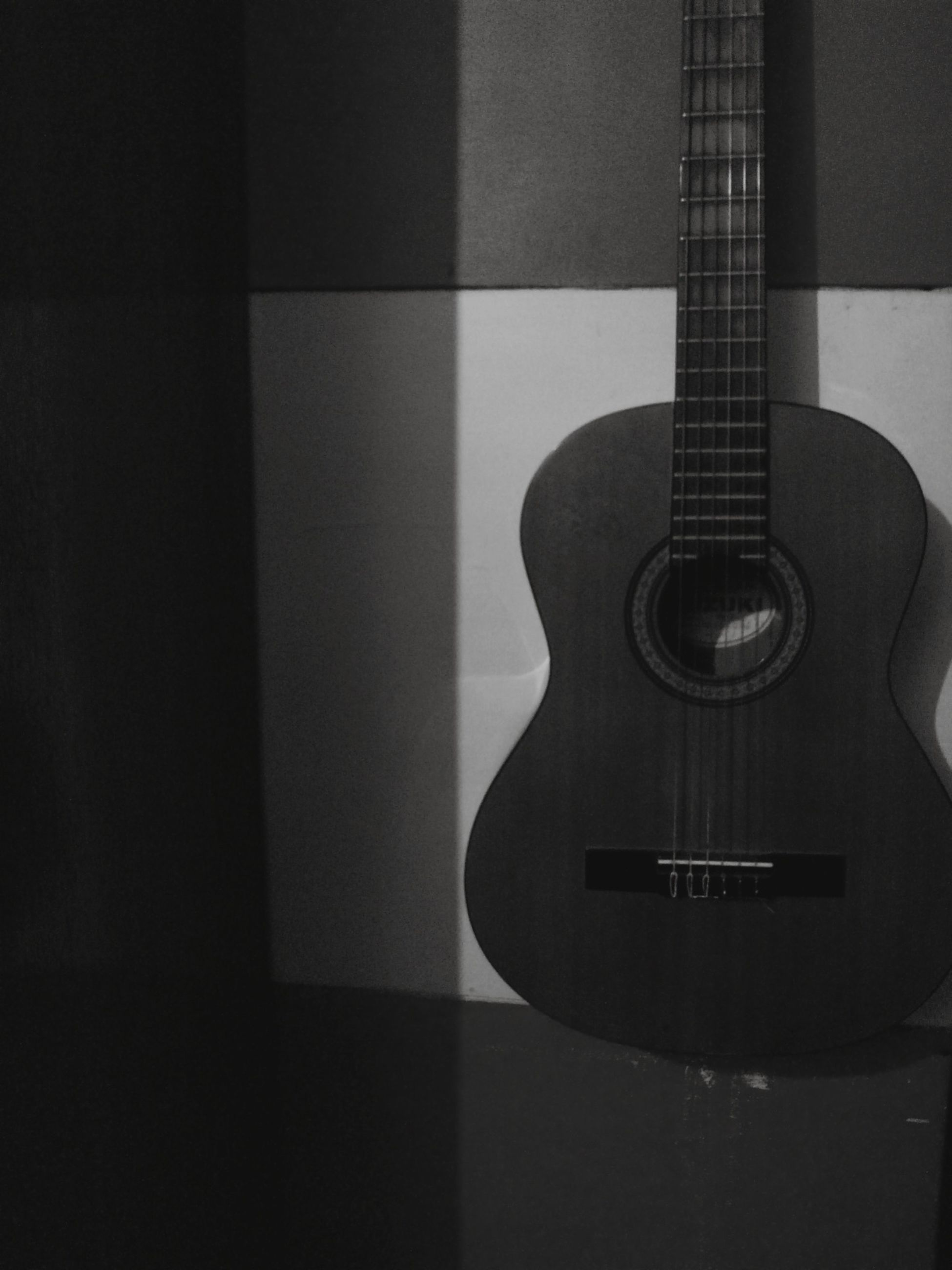 indoors, music, musical instrument, still life, guitar, arts culture and entertainment, technology, close-up, table, home interior, musical equipment, no people, wall - building feature, single object, musical instrument string, string instrument, metal, modern, shadow, acoustic guitar
