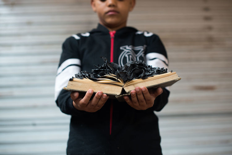 Conceptual portrait of a boy holding a burnt book
