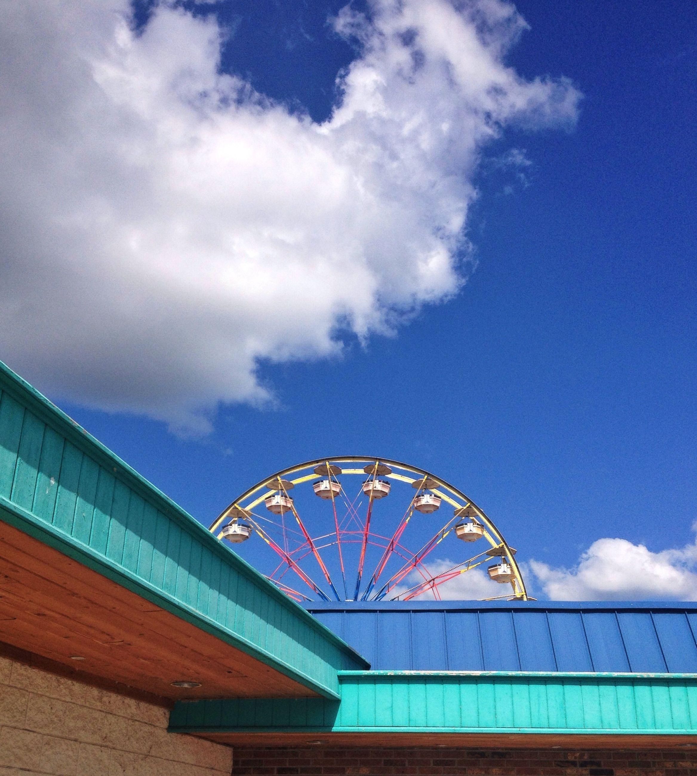 low angle view, sky, built structure, architecture, cloud - sky, blue, cloud, building exterior, cloudy, arts culture and entertainment, day, amusement park, outdoors, ferris wheel, no people, amusement park ride, high section, metal, pattern, design