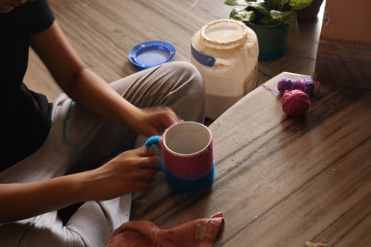 Midsection of woman holding drink on table diy at home