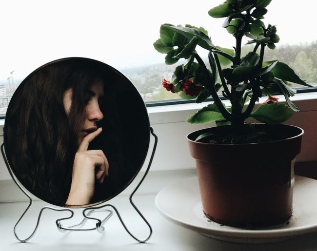 Close-up of woman looking at potted plant on table